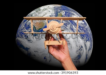 hand holding wood plane over the world,Elements of this image furnished by NASA