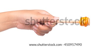 hand holding Wooden dipper for honey isolated on white background