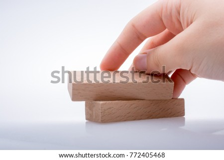 Hand holding wooden  domino on a white background
