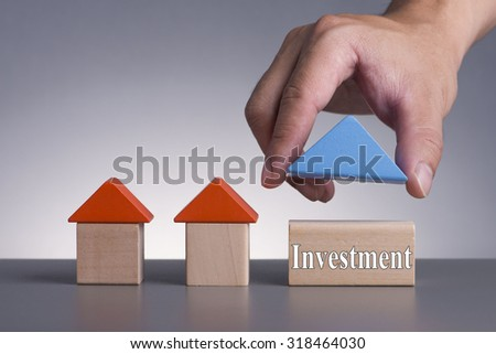 Hand holding wooden house (Housing Loan Concept) with word Investment - stock photo