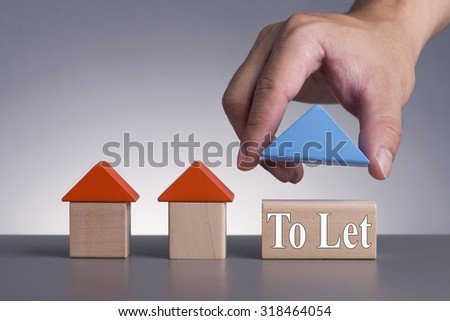Hand holding wooden house (Housing Loan Concept) with word To Let - stock photo
