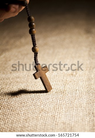 Hand holding wooden Rosary Beads on a beige background. - stock photo