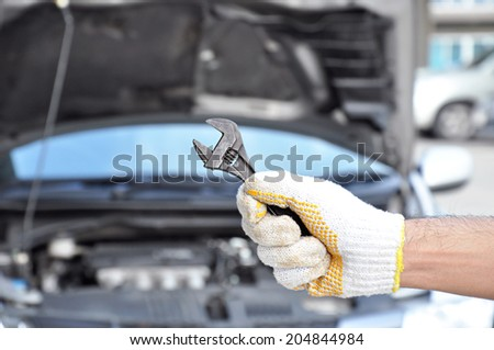 Hand holding wrench - car checking & repairing concept - stock photo