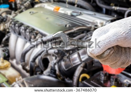 Hand holding wrench on blur car engine background