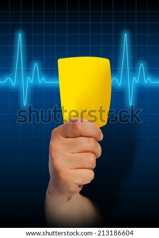 Hand holding yellow card on blue heart rate monitor expressing warning on heart condition, health hazard - stock photo