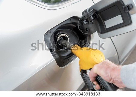 Hand holding yellow fuel pump nozzle and refilling car