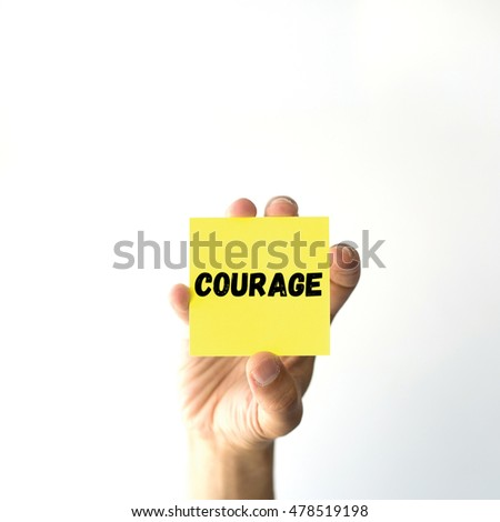 Hand holding yellow sticky note written COURAGE word