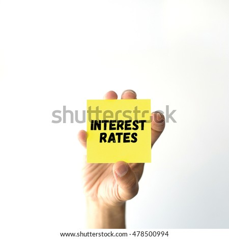 Hand holding yellow sticky note written INTEREST RATES word