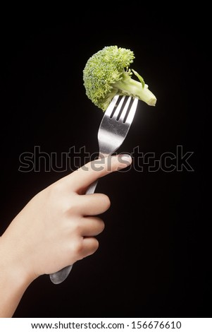Hand holds a fork and broccoli. - stock photo