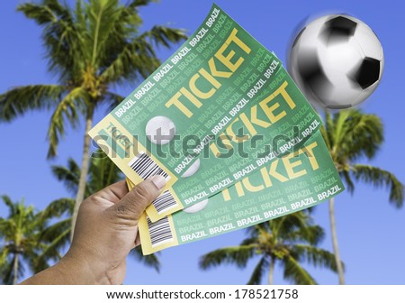 Hand holds a homemade soccer tickets on a beautiful day with many palm trees - stock photo