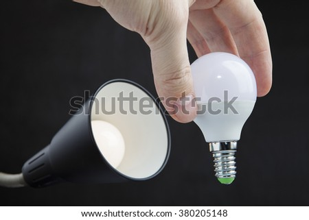 Hand holds a LED lamp low energy consumption, the exchange of light bulbs in floor lamp, dark background.