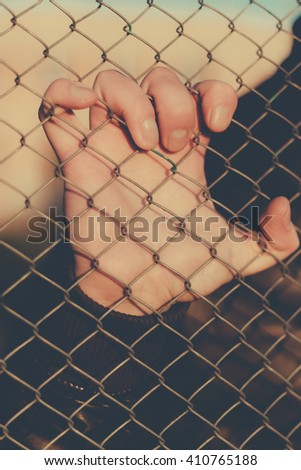 Hand holds a mesh fence. Outdoors photo.