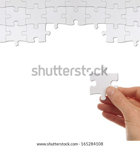 hand holds a part of a puzzles to solve it