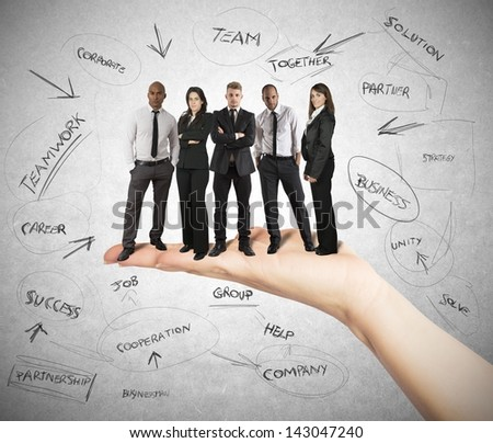 Hand holds a successful business team - stock photo