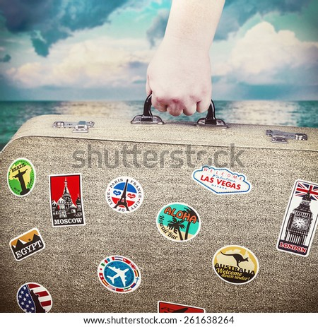 hand holds a suitcase with stickers on the background of the sea. toning image - stock photo