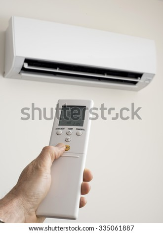 Hand holds an air condtioner remote control