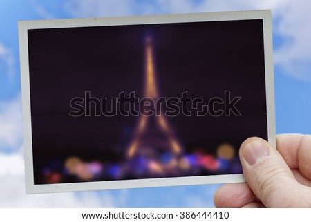 hand holds blurred snapshot of tour eiffel at night