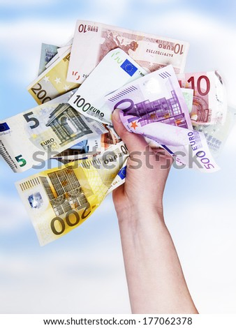 Hand holds bunch of crumpled cash