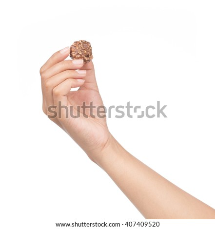 Hand holds Chocolate balls with almond isolated on white background - stock photo