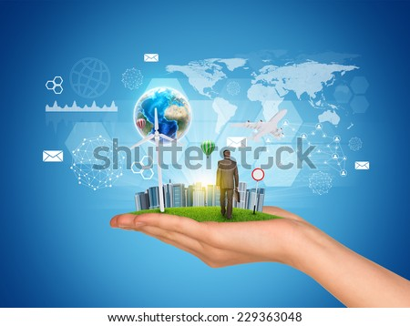 Hand holds city of skyscrapers on green grass and businessman walking forward. Earth and virtual elements near hand. Element of this image furnished by NASA - stock photo