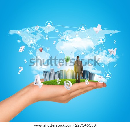 Hand holds city of skyscrapers on green grass and businessman walking forward. Fying letters and network with people icons near hand. Sky with clouds as backdrop - stock photo