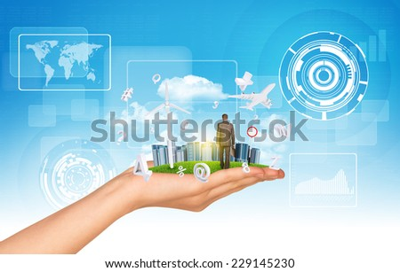 Hand holds city of skyscrapers on green grass and businessman walking forward. Fying letters near hand. Sky with clouds as backdrop - stock photo