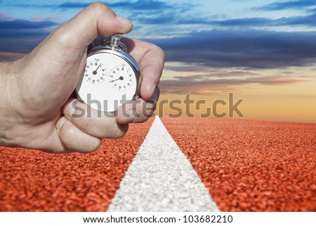 hand holds  historic stopwatch over racetrack - stock photo