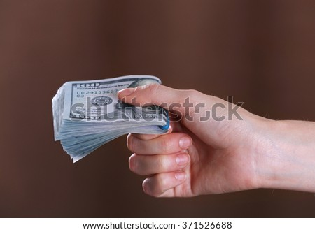 Hand holds money on brown background, close up