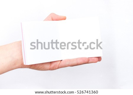 Hand holds notebook open. Blank white paper. Place for inscription, Clean place for new idea