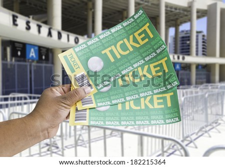 Hand holds soccer tickets in front of the Maracana Stadium - stock photo