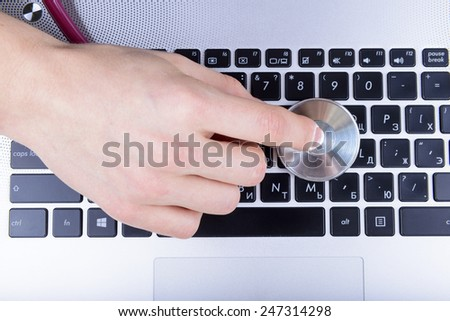 hand holds stethoscope on the laptop keyboard