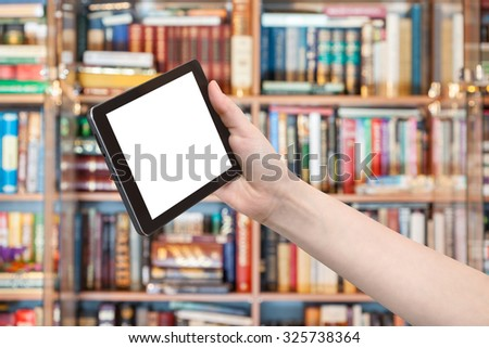 hand holds tablet pc with cut out screen and library on background - stock photo