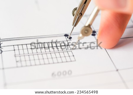 Hand holds the compass to create a drawing - stock photo
