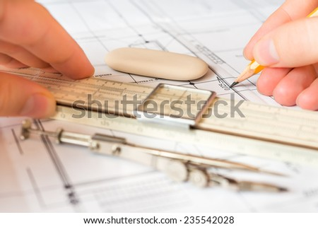 Hand holds the pencil and a slide rule to create a drawing, tools for sketching on the table. Angle view - stock photo