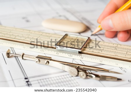 Hand holds the pencil to create a drawing, tools for sketching on the table. Angle view, focus on a slide rule - stock photo