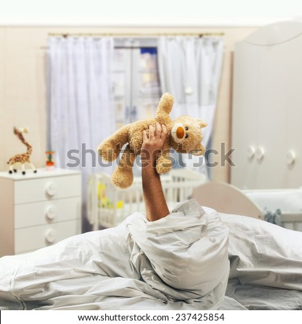 Hand holds toy bear above the bed - stock photo