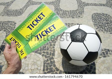 Hand holds two handmade tickets above football soccer ball in Rio de Janeiro - stock photo