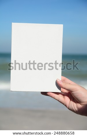 Hand holds white sheet on background of blue sky - stock photo