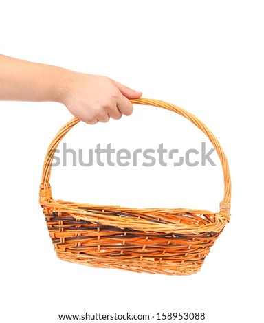 Hand holds wicker basket. Isolated on a white backgropund. - stock photo