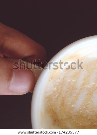 hand ilfts a cup of coffee