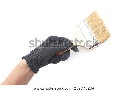Hand in a black working glove holding a paint brush, composition isolated over the white background - stock photo