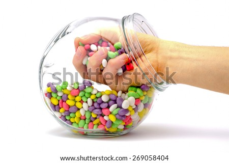 hand in a jar with colored candies isolated - stock photo