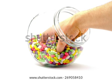 hand in a jar with colored candies on a white background - stock photo