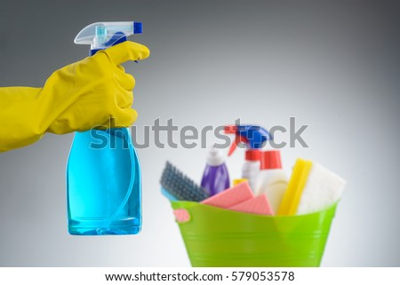 Hand in a rubber glove holding a spray bottle, close-up. Plastic basin with a fabric conditioner, a stain fighter, a toilet cleaning liquid, a sponge and a scrubber brush. Neutral background.