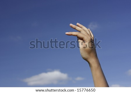 Hand in a throwing or catching position against blue sky.
