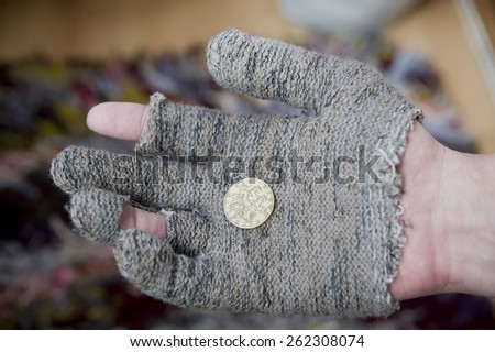hand in a torn glove and coins - stock photo