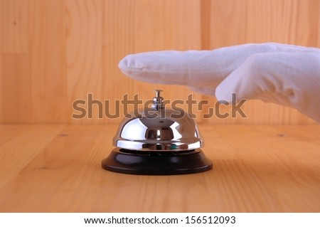 Hand in a white glove ringing the bell to call