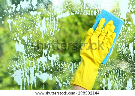 Hand in a yellow glove  wiping soap window with napkin  on the background of trees - stock photo