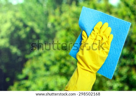Hand in a yellow glove  wiping  window with napkin  on the background of trees - stock photo