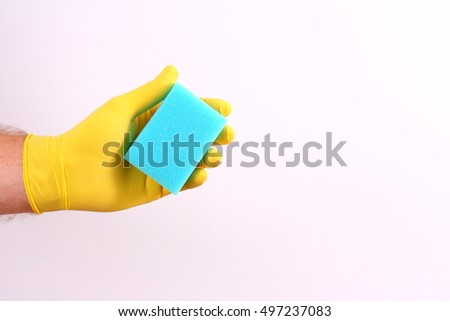 Hand in a yellow glove with sponge.